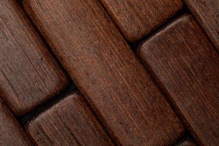 Dark wood texture in the shape of small rectangles (collection of natural and vegetal fibers). Foreground.