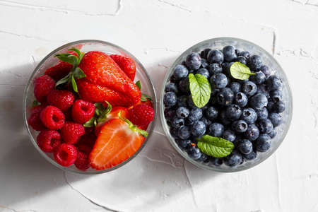 Appetizing variety of forest fruits (strawberries, large strawberries, raspberries, blueberries, red berries) in a glass bowl and mint leaves (peppermint, mint). On white textured background. Top view with copy space. Stock fotó