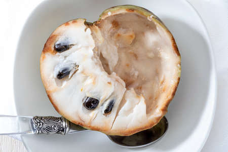 Close-up of ripe cherimoyas. Open fruit, with nuggets and spoon on light background. Stock fotó