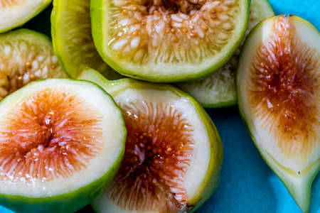 Whole and cut green figs, with honey. Foreground. On colorful background.