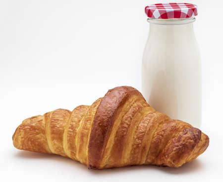 Croissant and bottle of milk for breakfast. Copy space. Isolated on white background.