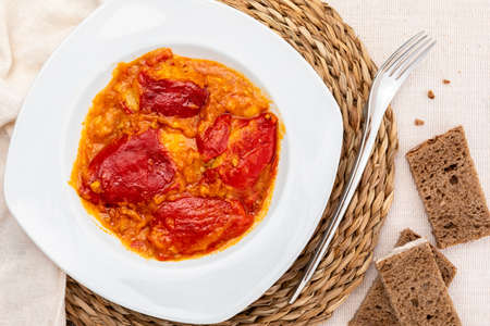 Peppers (del Piquillo) stuffed with meat or fish. Roasted red peppers and fillings made at home. Recipe of Spanish food and Mediterranean diet. With delicious sauce to spread bread and white rice.