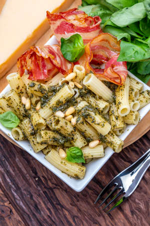 Macaroni with pesto (penne rigate). With onion and bacon, cheese, basil, pine nuts, garlic. On a wooden table with a rustic look.