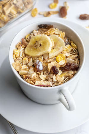 Bowl of milk with whole grains for breakfast. Muesli with dried fruits and dried fruits. On light background.