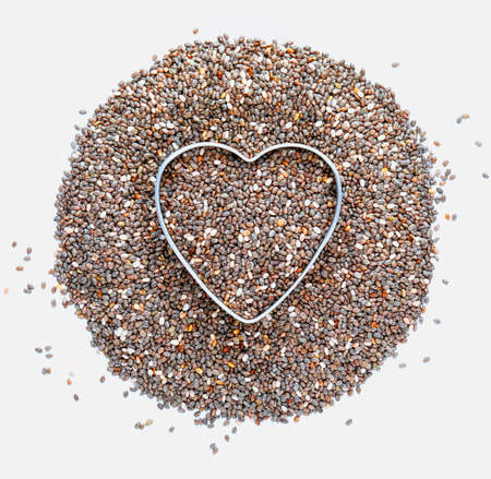 Heap of chia seeds with a heart. Love for chia. Isolated on white background. Macro close-up. With copy space.