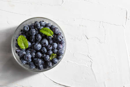 Delicious and appetizing blueberry berries in a glass bowl and mint leaves (peppermint, mint). On white textured background. Top view with copy space.
