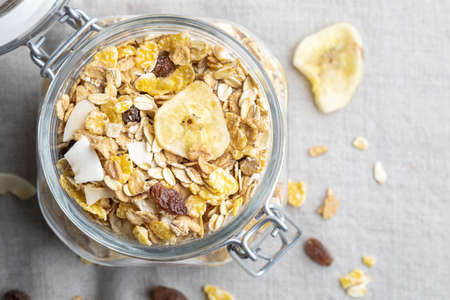 Glass jar with whole grains for breakfast. Muesli with dried fruits and dried fruits. With copy space. Top view.