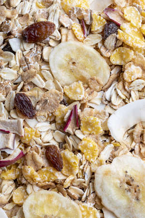 Texture with whole grains for breakfast. Macro close-up. Muesli with dried fruits and dried fruits. Vertical portrait. Stock fotó