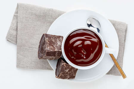 Cup of delicious thick drinkable hot chocolate with pure dark chocolate bars. Bowl with napkin and spoon isolated on white background and copy space.