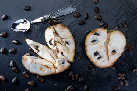 Mature cherimoyas. Open fruit, with nuggets and spoon on dark background.