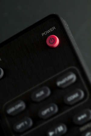 Close-up of Power button (on - off) on remote control for TV and audio in black color. With copy space.
