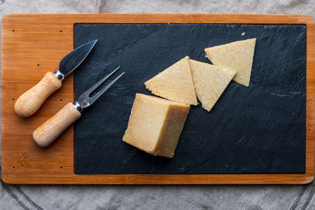 Cured sheep cheese. Cut into pieces on wooden board and black slate. Fork and knife for cheese. Top View.