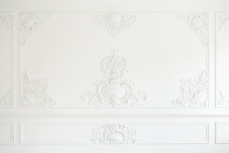 Beautiful ornate white decorative plaster mouldings in studio. The white wall is decorated with exquisite elements of plaster stucco. Stockfoto