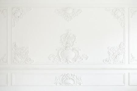 Schöne verzierte weiße dekorative Gipsformteile im Studio. Die weiße Wand ist mit exquisiten Stuckelementen verziert. Standard-Bild