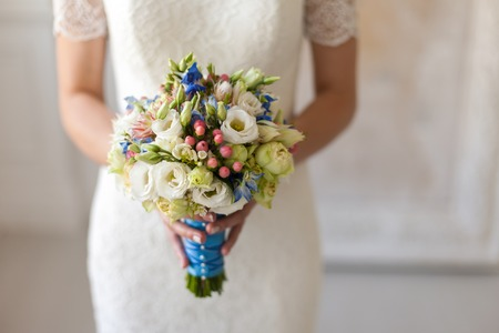 The bride is holding a wedding bouquet in her outstretched hands.