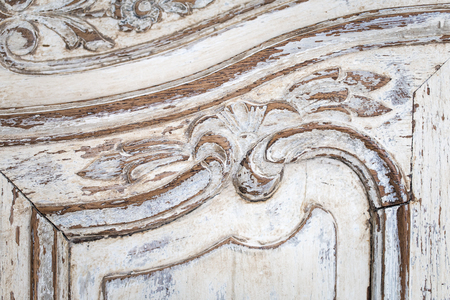 Vintage chest of drawers with carving white color with fading and metal handle. Close-up. Selective focus