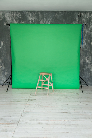 The working space of the photo studio with a green paper background and chair.