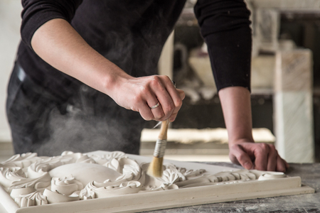 Hands of the sculptor with the tool. The sculptor works in the Studio. Creation of a decorative element from plaster. Luxurious stucco in Baroque style. Close up. Selective focus. Archivio Fotografico