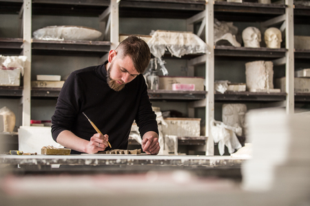 Sculptor works with concentration in the studio on a fragment of plaster sculpture. Abstract blur. Stock Photo