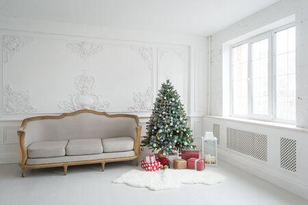 Interni barocchi luminosi di lusso con divano vintage e albero di Natale.