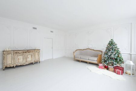 Luxurious bright interior with stucco walls, christmas tree, vintage chest of drawers and sofa.