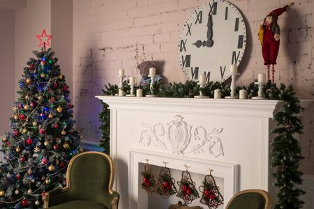 White fireplace with stucco patterns, candles, wach face, fir branches. Christmas decor. Close up. Selective focus.