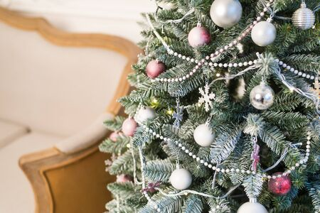 Christmas tree decorated with toys, balls and garland. Close up. Selective focus. Stock Photo