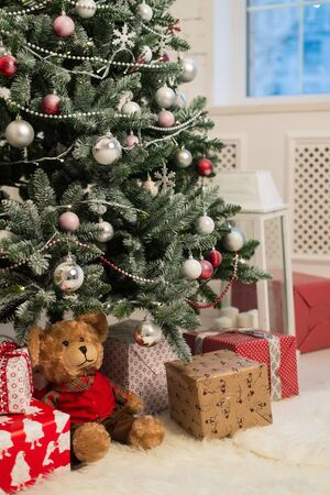 The decoration of the Christmas tree. Gifts, toys and candles. Selective focus. Close up.