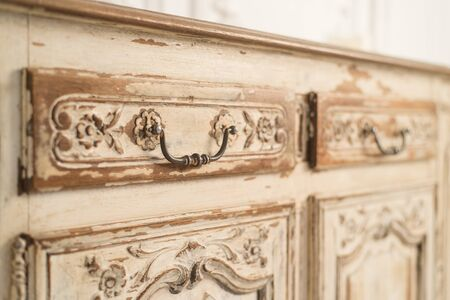 Luxurious bright interior with vintage chest of drawers. Close up. Selective focus.