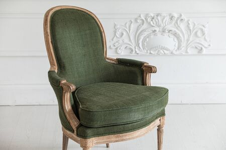 Vintage green armchair against the wall with plaster stucco patterns. Selective focus. Close up.