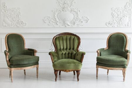Living room in the Rococo style. Vintage chairs against the wall with plaster stucco patterns. Selective focus.