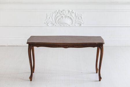 Vintage coffee table in the Rococo style with wood carvings in a luxurious interior with stucco. Selective focus.