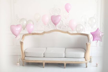 Luxury living room with sofa and stucco on the walls decorated with balloons for the holiday. Selective focus.