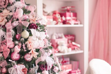 Elegant Christmas tree decorated with toys balls and ribbons in a bright interior. Soft focus. Imagens