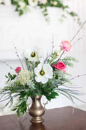 A bouquet of artificial flowers in a vase in the luxurious interior of the room. Soft focus.