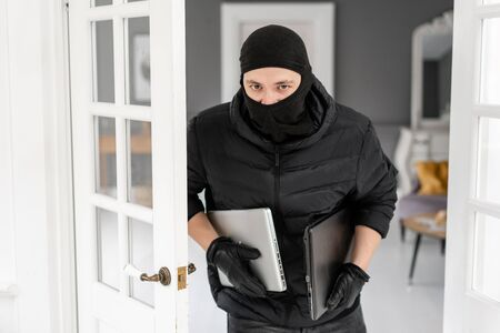 Thief looking at the camera with black balaclava stealing two modern expensive laptops. The burglar commits a crime in Luxury apartment with stucco.