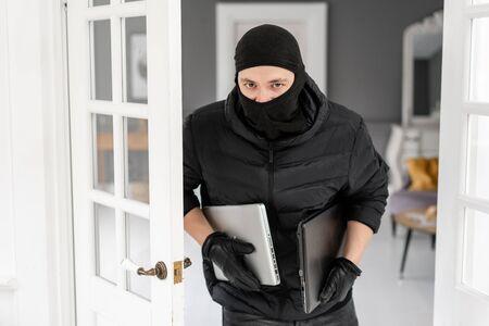 Voleur regardant la caméra avec une cagoule noire volant deux ordinateurs portables modernes et coûteux. Le cambrioleur commet un délit dans Appartement de luxe avec stuc.