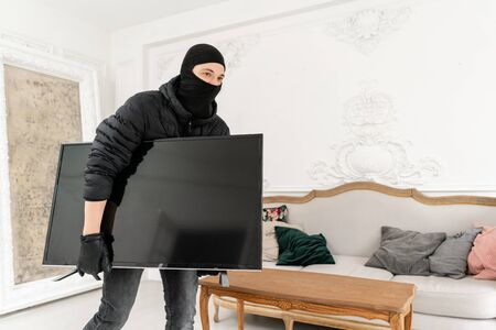 Man burglar stealing tv set from house. Thief with black balaclava stealing modern expensive television. Luxury apartment with stucco.