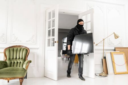 Thief with black balaclava stealing modern expensive television. Luxury apartment with stucco. Man burglar stealing tv set from house