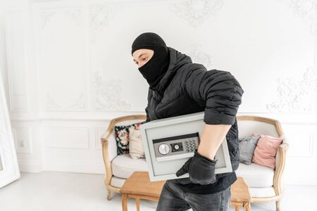 The burglar commits a crime in Luxury apartment with stucco. Thief with black balaclava stealing modern Electronic safe box.