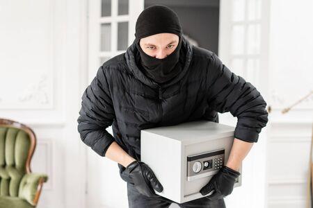 Voleur regardant la caméra avec une cagoule noire volant un coffre-fort électronique moderne. Le cambrioleur commet un délit dans Appartement de luxe avec stuc.