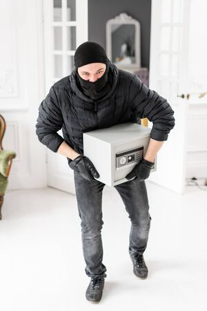Thief looking at the camera with black balaclava stealing modern Electronic safe box. The burglar commits a crime in Luxury apartment with stucco.