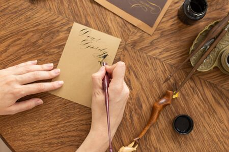 Calligrapher is holding a pen with ink. The girl writes a letter in handwritten font. Creative workshop of the artist. Soft focus.