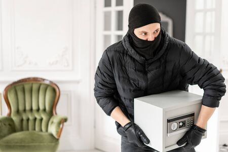 Thief with black balaclava stealing modern Electronic safe box. The burglar commits a crime in Luxury apartment with stucco.
