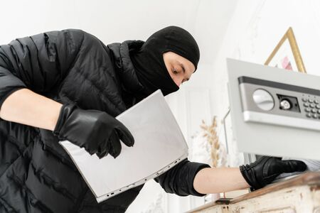 Thief with black balaclava stealing modern Electronic safe box. The burglar commits a crime in Luxury apartment with stucco. Stock Photo