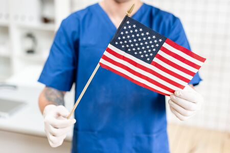 Young doctor man holding an american flag in the hospital