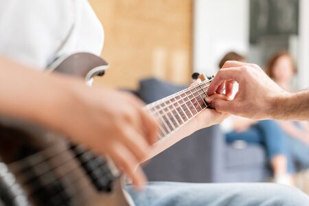 Young boy moves his hand along guitar strings while his father helps boy to take chords Stock Photo