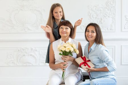 An elderly woman with flowers and a gift in her hands surrounded by her daughter and granddaughter 写真素材