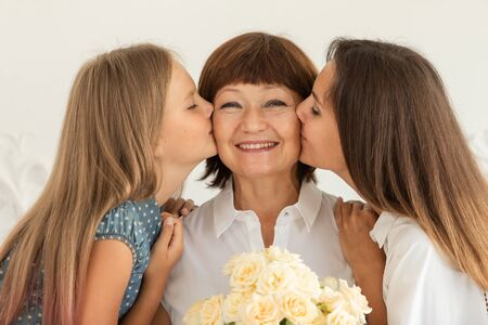 Grandmother holding flowers in hands, her daughter and granddaughter hug each other and smile