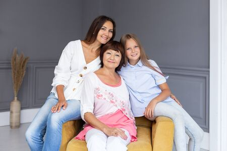 Daughter, mother and grandmother sit in chair and smiling